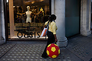 A woman carries an oversize football of red and yellow past an Oasis fashion store in Regent Street.