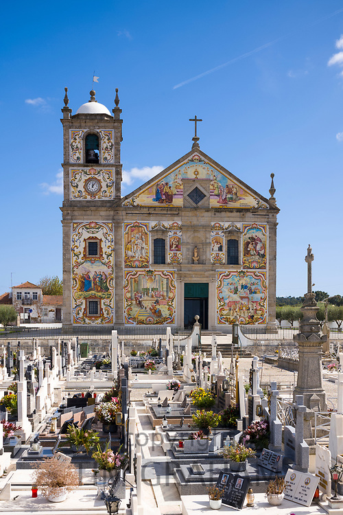 Church decorated with traditional tiles depicting religious scenes and graveyard at Valega near Ovar in Portugal