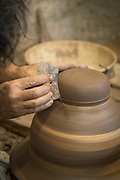 Potter working on fresh clay shaping object.