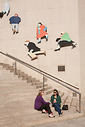 """Two women relaxing near the Royal Bank of Canada, by a public sculpture by Catherine Widgery entitled """"City People""""."""