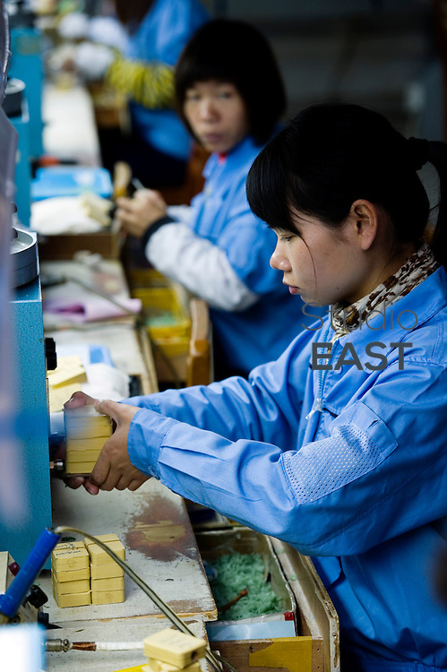 A worker sculpts rubber molds in a jewel factory, in the district of Panyu of Guangzhou city, Guandong province, China, on January 26, 2011. In Panyu, more than 200 jewelry companies, mainly from Hong Kong, have set up manufacturing factories, employing more than 50,000 workers. The district processes more than 100 tons of gold and platinum every year, with a total production value of 5 billion yuan (US$604 million) and an export volume of US$800 million. (Photo by Lucas Schifres/Getty Images)