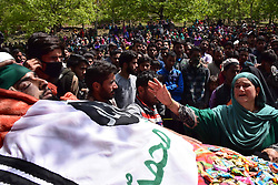 April 25, 2018 - Pulwama, Jammu & Kashmir, India - (EDITORS NOTE: Image contains graphic content.) A Kashmiri woman tries to touch the body of Ishfaq Ahmed during his Funeral procession at his residence Handura Village of Tral in south Kashmir's Pulwama District. Ishfaq Ahmed was a local militant who got killed along with his 3 Associates in a 12 hour long gunfight. Thousands of people including men, women and children attended the funeral procession of Ishfaq Ahmed on Wednesday in Tral Some 50 kms away from Srinagar summer capital of Indian Kashmir. Two security forces were also killed and two army men wounded in the gunfight. (Credit Image: © Abbas Idrees/SOPA Images via ZUMA Wire)