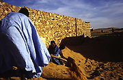 A man digs himself out of his house in the morning after the wind has blown sand and covered his doorway during the night.<br /> Chinguetti is slowly being buried by the sand from the Sahara Desert