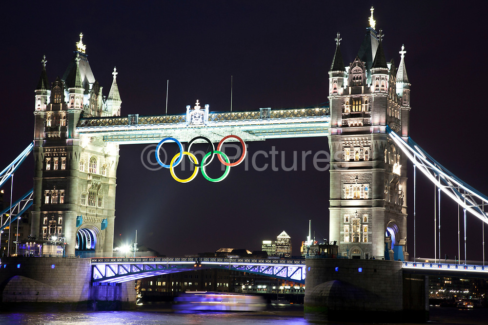 Giant Olympic rings on Tower Bridge to mark the countdown to the London 2012 Games. The rings, 25 metres wide and 11.5 metres tall, were lowered into place on the central London landmark on the River Thames with the public gathering on the river path in the evening light. The rings, which weigh three tonnes, cost £259,817 to produce and installing them is estimated to have cost £53,000.