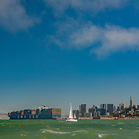 A sailboat passes a heavily loaded container ship approaching the Bay Bridge in San Francisco Bay, California.
