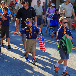 Lititz, PA / USA - July 3, 2017:   Cubs scouts give away candy during a patriotic parade in a small American town at a 4th of July Independence Day celebration.