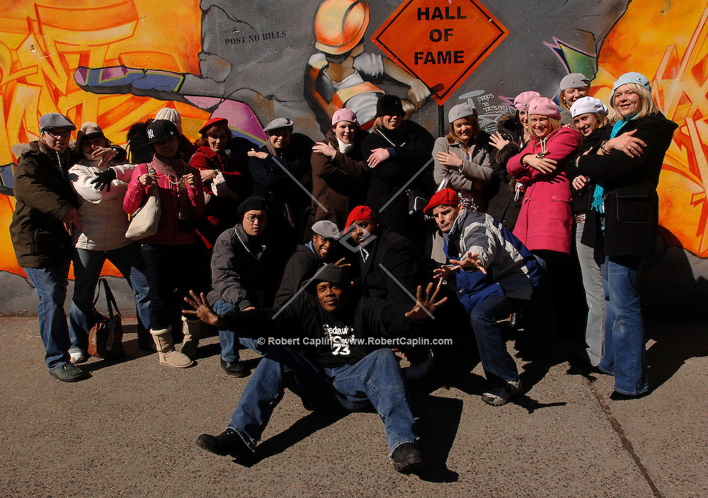 """Hip-hop pioneer """"The Mighty Mike C"""" of The Fearless 4 (C) takes group photos with tourists at The Graffiti Hall of Fame in Harlem as part of Hush Tours' Hip-Hop Tour March 4, 2006."""
