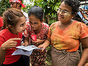 25 OCTOBER 2015 - SHWEPYITHAR, MYANMAR: A National League for Democracy supporter explains voting to people in Shwepyithar, Myanmar, while a NLD motorcade drives through the village. Political parties are in fill campaign mode in Myanmar (Burma). National elections are scheduled for Sunday Nov. 8. The two principal parties are the National League for Democracy (NLD), the party of democracy icon and Nobel Peace Prize winner Aung San Suu Kyi, and the ruling Union Solidarity and Development Party (USDP), led by incumbent President Thein Sein. There are more than 30 parties campaigning for national and local offices.     PHOTO BY JACK KURTZ