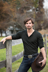 cowboy holding his hat by a wooden fence