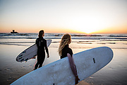 Surfers standing with their surfboards at the waters edge at sunset, ready to go surfing at St Ouen's Bay, Jersey, CI with view out to La Rocco Tower