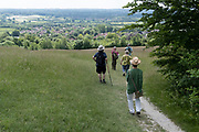 A group of walking friends on a public footpath, descend the contours of the escarpment that overlooks the Kent village of Kemsing, on 13th June 2021, in Kemsing, Kent, England.