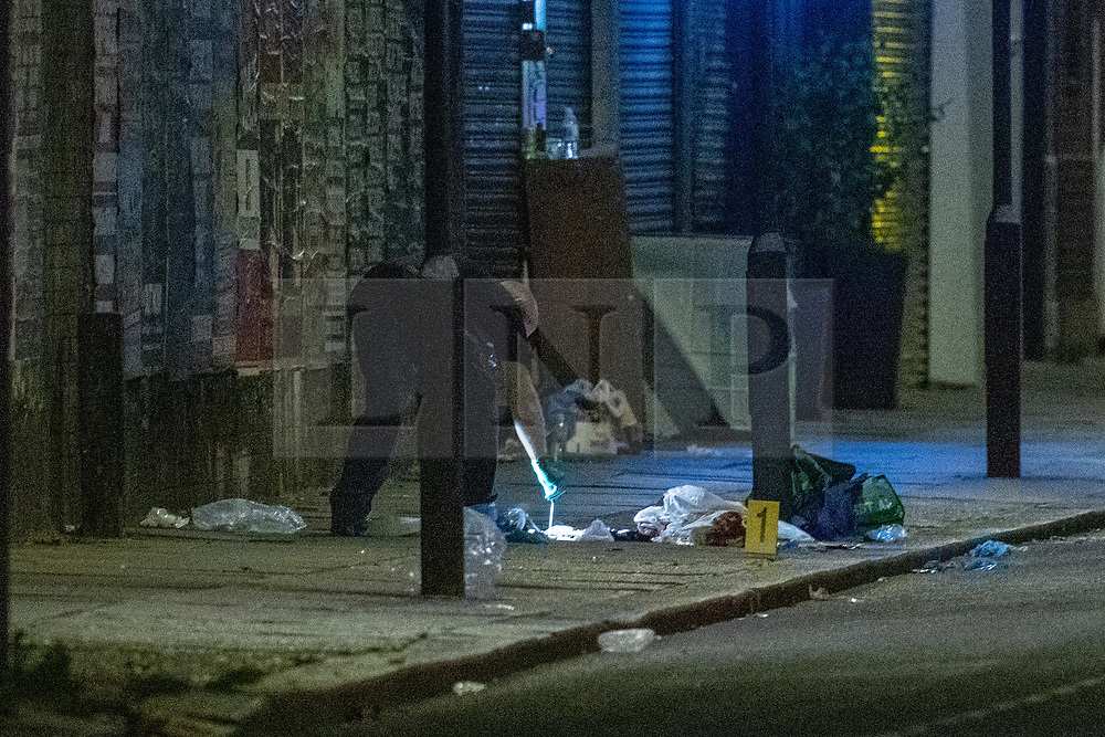 © Licensed to London News Pictures. 26/06/2020. London, UK. A forensic investigator uses a swab to take a evidence sample around medial kits left by paramedics indicated by an evidence identification marker inside the police cordon. A person has been stabbed on Du Cane Road in East Acton on Thursday 25th June 2020. A cordon closed off a large section of the road underneath a railway bridge where two vehicles remained. Photo credit: Peter Manning/LNP