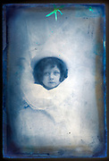 glass plate with child portrait  wrapped around newspapers France ca 1910s