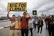 Supporters and protesters hold up their banners and placards on Millennium Bridge at the Rise For Climate Change event held outside Tate Modern in London, England, United Kingdom on September 8th 2018. Tens of thousands of people joined over 830 actions in 91 countries under the banner of Rise for Climate to demonstrate the urgency of the climate crisis. Communities around the world shined a spotlight on the increasing impacts they are experiencing and demanded local action to keep fossil fuels in the ground. There were hundreds of creative events and actions that challenged fossil fuels and called for a swift and just transition to 100% renewable energy for all. Event organizers emphasized community-led solutions, starting in places most impacted by pollution and climate change. Photographed for 350.org.