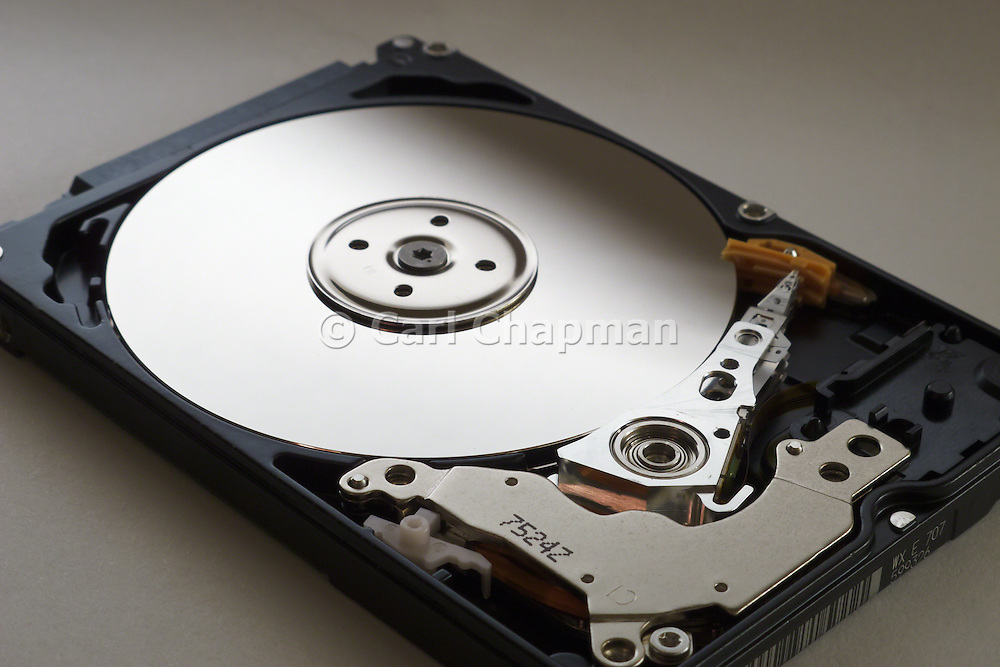 Inside an open data storage computer portable hard disk drive. View of spindle and arm. <br /> <br /> Editions:- Open Edition Print / Stock Image