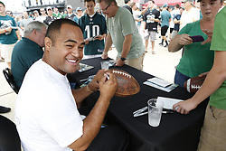 Former Philadelphia Eagles Reno Mahe signs an autograph on a football in the Head House Plaza before the NFL football training camp in Philadelphia, Sunday, July 28, 2013. (Photo by Brian Garfinkel)