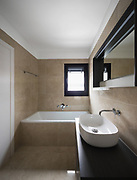 Bathroom with large marble tiles. Detail of sink and bathtub.