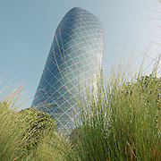 The leaning tower of Capital Gate are another example of daring and futuristic architecture. Building is seen through blades of grass.