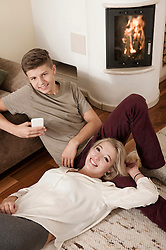 Teenage couple relaxing on carpet in front of fireside