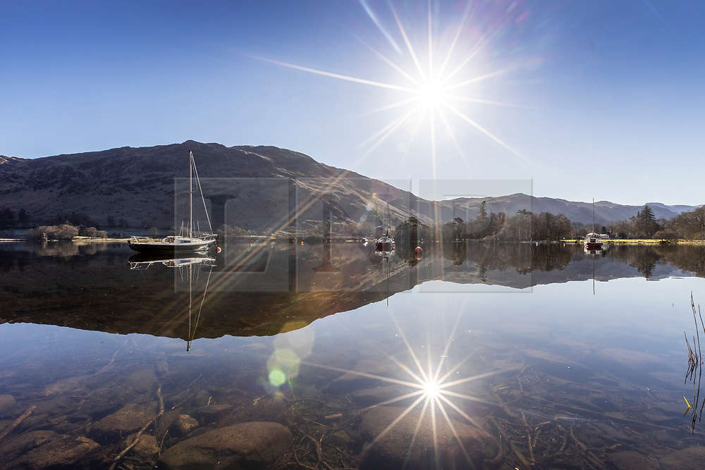 © Licensed to London News Pictures. 12/04/2021. Glenridding UK. The boats & surrounding hills reflect into the still water of Ullswater lake in Glenridding as the day gets off to a sunny start in Cumbria this morning. Photo credit: Andrew McCaren/LNP