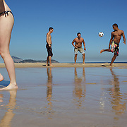 Locals play football on Ipanema beach, Rio de Janeiro, Brazil. 6th July 2010. Photo Tim Clayton..The beaches of Rio de Janeiro, provide the ultimate playground for locals and tourists alike. Beach activity is in abundance as beach volley ball, football and a hybrid of the two, foot volley, are played day and night along the length and breadth of Rio's beaches. .Volleyball nets and football posts stretch along the cities coastline and are a hive of activity particularly at it's most famous beaches Copacabana and Ipanema. .The warm waters of the Atlantic Ocean provide the ideal conditions for a variety of water sports. Walkways along the edge of the beaches along with exercise stations and cycleways encourage sporting activity, even an outdoor gym is available at the Parque Do Arpoador overlooking the ocean. .On Sunday's the main roads along the beaches of Copacabana, Leblon and Ipanema are closed to traffic bringing out thousands of people of all ages to walk, run, jog, ride, skateboard and cycle more than 10 km of beachside roadway. .This sports mad city is about to become a worldwide sporting focus as they play host to the world's biggest sporting events with Brazil hosting the next Fifa World Cup in 2014 and Rio de Janeiro hosting the Olympic Games in 2016...