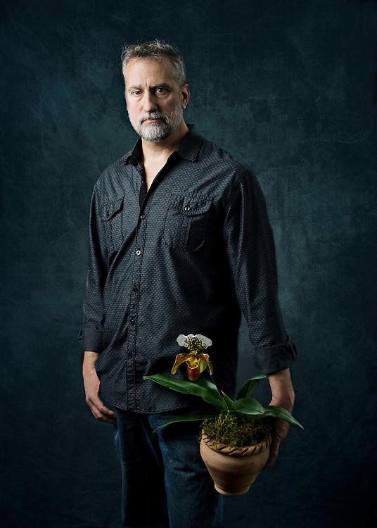 Studio Portrait of Josef, florist and owner of Floral Botanical Design holding an orchid