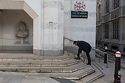 A City businessman bends down to tie a shoelace outside the Guildhalls Art Gallery on 13th February 2017, in the City of London, United Kingdom. The Guildhalls Art gallery was established in 1886 as a Collection of Art Treasures worthy of the capital city, and includes works dating from 1670 to the present, including 17th-century portraits, Pre-Raphaelite masterpieces and a range of paintings documenting Londons dramatic history.