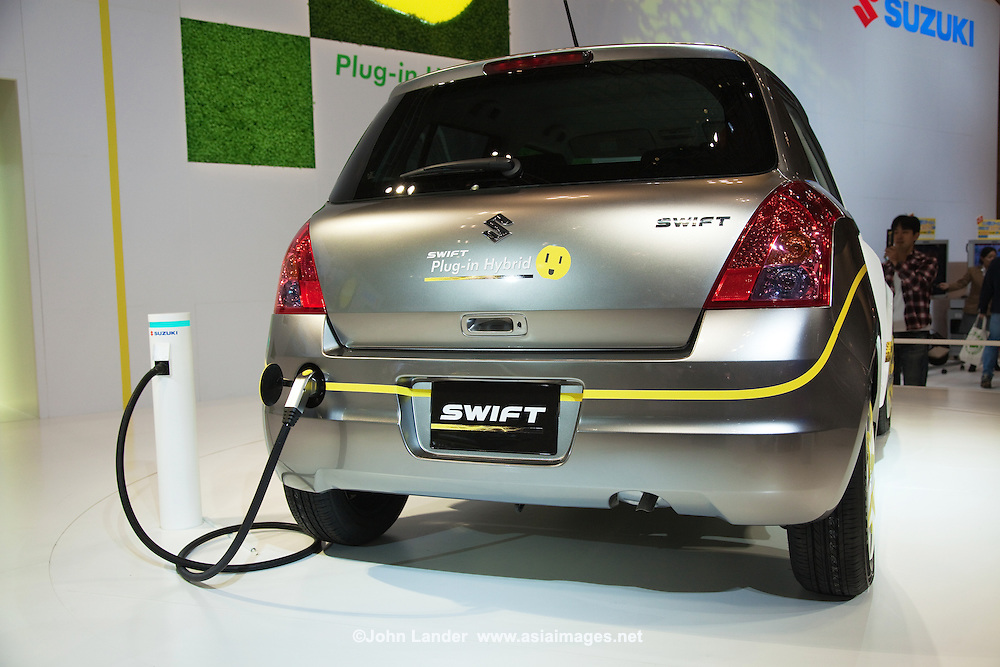"""Nissan's new electric car SX4 showing at the Tokyo Motor Show - a biennial auto show held in October or November at the Makuhari Messe event space in Japan for cars, motorcycles and commercial vehicles. Hosted by the Japan Automobile Manufacturers Association (JAMA)  it is a recognized international show by the Organisation Internationale des Constructeurs d'Automobiles, and normally sees more concept cars than actual production car introductions. The press see the show as one of the big five along with Detroit, Geneva, Frankfurt and Paris.   In 2009 new hybrids and electric vehicles from Japan's leading automakers dominate the show. Toyota Motor Corporation introduced its 1/X concept vehicle, a Prius-like sedan that has a third of the weight of the Prius and obtains double the Prius' fuel economy. The vehicle cuts its weight by using carbon fiber reinforced plastic in its frame and boosts fuel economy with a small plug-in hybrid powertrain that can be fueled with either gasoline a blend of 85% ethanol and 15% gasoline. Toyota's other plug-in hybrid concept, the Hi-CT, is a small, boxy, two-door vehicle aimed at the youth market.   Among the other automakers, Honda Motor Company, Ltd., unveiled the CR-Z, a """"next-generation lightweight sports car"""" that features Honda's hybrid electric drivetrain, and the PUYO, another small, boxy vehicle, powered by a fuel cell. Honda will also unveil the one-wheeled scooter transport, the Honda U3-X.  While Nissan unveiled the Pivo 2, a small electric vehicle with a lithium-ion battery pack and wheel motors.."""
