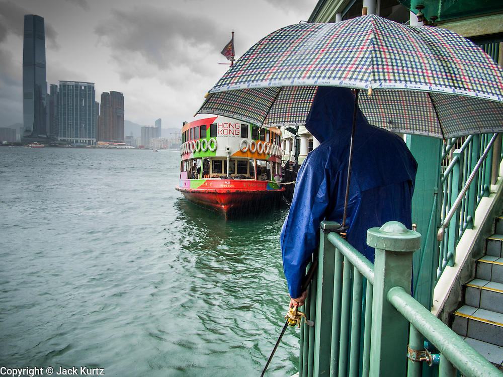 13 AUGUST 2013 - HONG KONG:  A man fishes off the Star Ferry pier during Typhoon Utor in Hong Kong. Typhoon Utor (known in the Philippines as Typhoon Labuyo) is an active tropical cyclone located over the South China Sea. The eleventh named storm and second typhoon of the 2013 typhoon season, Utor formed from a tropical depression on August 8. The depression was upgraded to Tropical Storm Utor the following day, and to typhoon intensity just a few hours afterwards. The Philippines, which bore the brunt of the storm, reported 1 dead in a mudslide and 23 fishermen missing at sea. The storm brushed by Hong Kong bringing several millimeters of rain and moderate winds to the island but causing no reported damage or injuries. It is expected to make landfall in China.  PHOTO BY JACK KURTZ