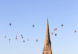 © Licensed to London News Pictures. 07/06/2015. London, UK. Hot air balloons rise over a church in Blackheath south east London on a summer morning. 50 Balloons took to the skies as part of the Lord Mayor's Regatta to raise money for charity. the last mass ascent balloon flight over London was over 20 years ago.Photo credit : Stu Mayhew/LNP