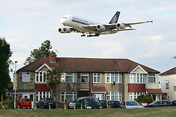 © Licensed to London News Pictures. 17/12/13. London, UK Extra runways at Heathrow and Gatwick airports are among the options put forward by the Government-appointed Airports Commission in its first report today 17th December 2013.  FILE PICTURE DATED 01/02/2011. A plane flies over houses as it comes into land at Heathrow Airport in London, UK. Photo credit : Jim Preston/LNP