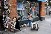 Woman stops to let her small dog have a drink of water outside a pet shop on the Kings Road in the upmarket area of Chelsea on 14th April 2021 in London, United Kingdom. Chelsea is one of the principal areas for exclusive, luxury goods in West London. It is known as a district where the rich and wealthy shop, mostly for high end fashion and jewellery.