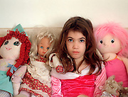Young female child of 7 surrounded with dolls