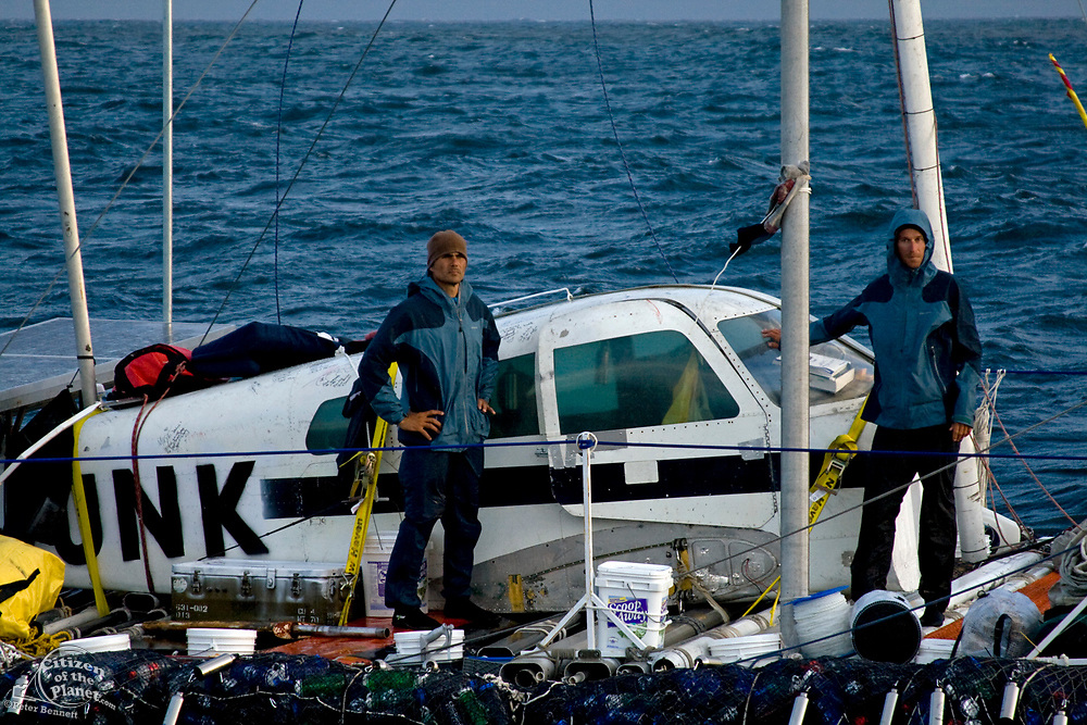 """On the thrid day of the trip, with gale force winds approaching, the """"Junk"""" finds refuge in a cove off San Nicholas Island. Marcus (l) and Joel (r) prepare for their first night alone without their escort, the Alguita. On Sunday June 1, the raft named """"Junk""""  left Long Beach for it's 2100 mile voyage to Hawaii to bring attention to the plastic marine debris (nicknamed the plastic soup) accumulating in the North Pacific Gyre. The raft was designed and will be sailed by Dr. Marcus Eriksen of the Algalita Marine Research Foundation, and Joel Paschal, it is constructed from 15,000 plastic bottles, an airplane fuselage, discarded fishing nets and a solar generator. The raft was towed for two and a half days to near San Nicholas Island, about 65 mile of the coast of California, so it could catch favorable winds for it's trip. The tow boat was the ORV Alguita, captained by Charlie Moore of the Algalita Marine Research Foundation, the man credited for first discovering the plastic soup in the Gyre over 12 years ago."""