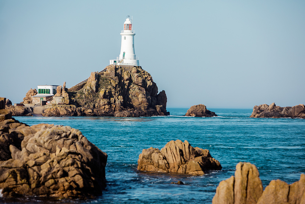 Corbiere lighthouse, the tourist attraction and landmark in Jersey, Channel Islands, surrounded by calm blue sea at high tide in summer.