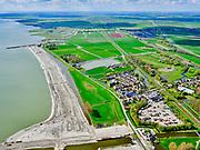 Nederland, Noord-Holland, gemeente Koggenland; 07-05-2021; Hoogheemraadschap Hollands Noorderkwartier, Scharwoude met gemaal Westerkogge onder in beeld. Aan de IJsselmeerdijk is het dijkmagazijn zichtbaar (rood pannendak, zwart geteerd). In het kader van de dijkverbetering wordt er een oeverdijk aangelegd, de nieuwe halfhoge dijk heeft een buitentalud wat voor de bestaande dijk aangebracht wordt. <br /> Water board Hollands Noorderkwartier, Scharwoude with Westerkogge pumping station at the bottom of the picture. The dike warehouse is visible on the IJsselmeerdijk (red tiled roof, black tarred). As part of the dyke improvement, an embankment dyke is being constructed, the new half-height dyke has an outer slope which will be installed in front of the existing dyke.<br /> <br /> luchtfoto (toeslag op standard tarieven);<br /> aerial photo (additional fee required)<br /> copyright © 2021 foto/photo Siebe Swart