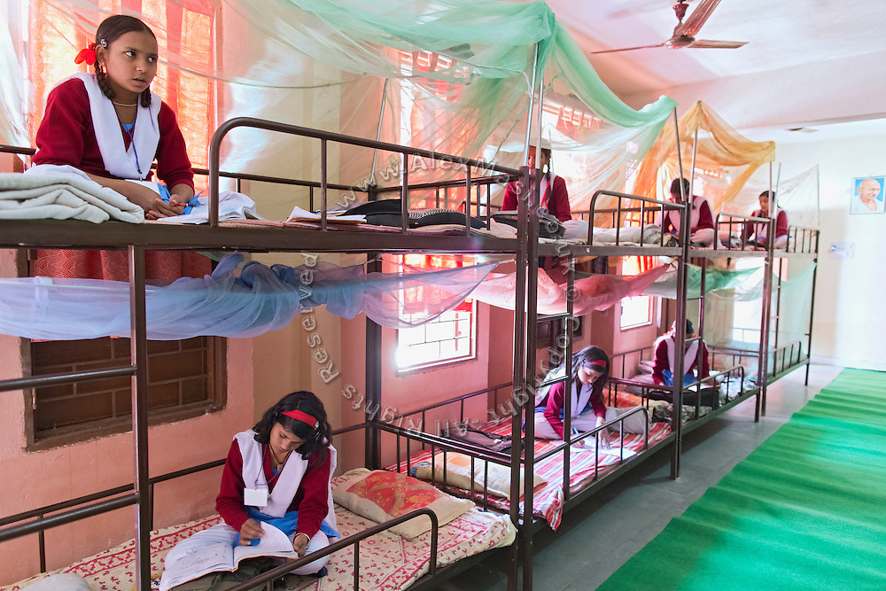 Ritu Gaur, 13, (bottom left) is studying on her bed inside a dorm of the Jamoniya Tank Girls Hostel, near Sehore, Madhya Pradesh, India, where the Unicef India Sport For Development Project has started in 2012. Covering 313 state-run girls' hostels and 207 mixed hostels in Madhya Pradesh, the project ensures that children from Scheduled Tribes (ST) and others amongst the poorest people in India, can easily access education and be introduced to sports. Field workers from Unicef also oversee their nutrition and monitor the overall conditions of each pupil.