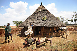 The groomsmen for Alelegn, 23, dance outside the hut where he was waiting for his bride, Leyualem, 14, in the Amhara Region, Ethiopia on May 23, 2007.  Leyualem had never met her husband before her wedding day, yet sumitted as they bound her in the white wedding cloth. The men later said it was placed over her head so she would not be able to find her way back home, should she want to escape the marriage.