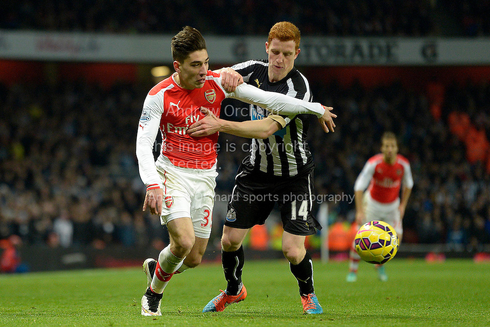 Hector Bellerin of Arsenal is held by Jack Colback of Newcastle United. Barclays Premier league match, Arsenal v Newcastle Utd at the Emirates Stadium in London on Saturday 13th December 2014.<br /> pic by John Patrick Fletcher, Andrew Orchard sports photography.