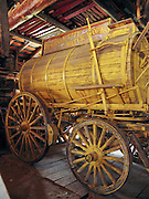 """An antique yellow-painted wooden water tank wagon of the """"Virginia City Water Works"""" is preserved at Nevada City, Montana, USA. Nevada City was a booming placer gold mining camp from 1863-1876, but quickly declined into a virtual ghost town. This fascinating town inspires you to imagination what life must have been like in early Montana when gold was discovered at nearby Alder Gulch. More than 90 buildings from across Montana have been gathered for preservation at Nevada City, mostly owned by the people of the State of Montana, and managed by the Montana Heritage Commission. In 2001, the excellent PBS television series """"Frontier House"""" used one of the buildings and its furnishings to train families in re-creating pioneer life. A miner's court trial and hanging of George Ives in the main street of Nevada City was the catalyst for forming the Vigilantes, a group of citizens famous for taking justice into their own hands in 1863-1864. Directions: go 27 miles southeast of Twin Bridges, Montana on Highway 287."""