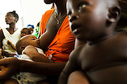 A woman breast feeds her child while they wait at the under-5 clinic at the Bonthe district hospital in Bonthe, Sierra Leone on Thursday April 22, 2010.