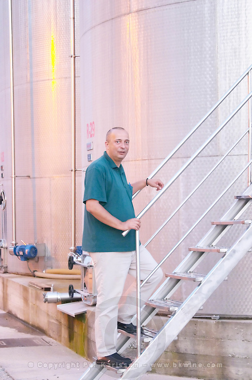 Daniel Lay manager from the winery. In front of outside stainless steel fermentation tanks. Hercegovina Produkt winery, Citluk, near Mostar. Federation Bosne i Hercegovine. Bosnia Herzegovina, Europe.