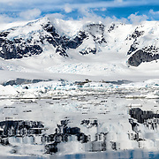 Mountains, ice, snow, and reflections on the water in a scenic landscape on the Antarctic Peninsula.