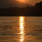The setting sun is reflected on the rippled water at sunset on the Mekong River near Luang Prabang, Laos.