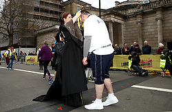 A volunteer presents a runner with a finishers medal after the 2018 London Landmarks Half Marathon. PRESS ASSOCIATION Photo. Picture date: Sunday March 25, 2018. Photo credit should read: John Walton/PA Wire