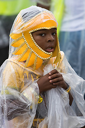 London, August 28th 2016. A little boy in a rain cape stares at the camera as Europe's biggest street party, the Notting Hill Carnival gets underway.