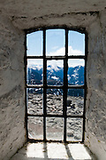 """Window to a wild rocky alpine landscape. Ascend to Skålatårnet (""""Skåla tower"""" or Kloumanntårnet, 1843 meters / 6047 feet elevation) on Skåla, the highest tidewater mountain in Norway.  Doctor Kloumann built the tower in 1891 with hopes to cure clients with tuberculosis. The hike starts east of Loen village in Stryn municipality, Sogn og Fjordane county, Norway. Between Tjugen camping and Loenvatnet, park at the pay lot and ascend steeply on a well marked trail. Stepping stones greatly improve footing on the upper portion protected within Jostedalsbreen National Park (nasjonalpark). Hikers allow at least 5 hours up and 3 hours down on this strenuous ascent of 1800 meters (6000 feet). For a fee, the public can sleep in the tower's 22 beds, as administered by Bergen Turlag, a subsidiary of the Norwegian Trekking Association (DNT)."""