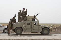 © Licensed to London News Pictures. 11/09/2015. Kirkuk, Iraq. Kurdish peshmerga watch from the top of an armoured humvee during an offensive by the peshmerga to expand a safety zone around Kirkuk, Iraq.<br /> <br /> The offensive, which went unchallenged after ISIS left the area ahead of the attack, saw the peshmerga capture 15 villages along the Kirkuk front line. The objective of the offensive was to expand the safety zone around Kirkuk, stopping militants from firing missiles and rockets in to the city of Kirkuk. 3 peshmerga were killed and 24 wounded due to improvised explosive devices left behind by the militants. Photo credit: Matt Cetti-Roberts/LNP