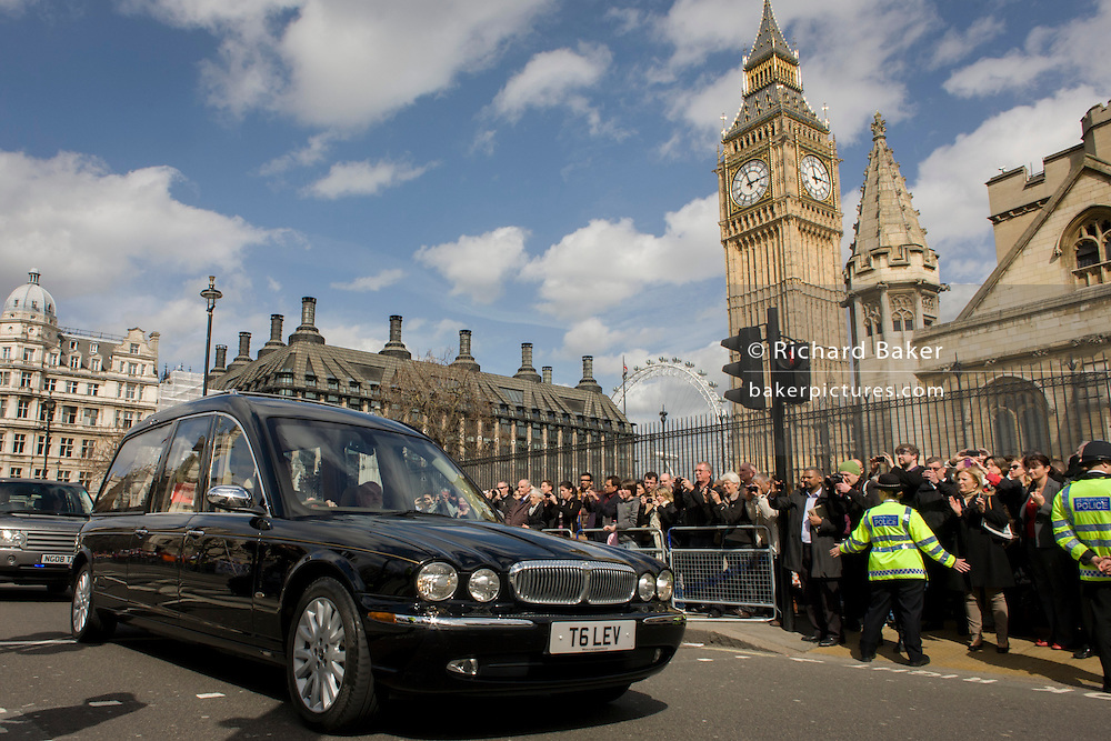 Draped in the Union flag, ex-British Prime Minister Baroness Margaret Thatcher's coffin travels along St Margaret's Street towards the Palace of Westminster in London for the last time. Her body is due to spend the night beneath Parliament in the Chapel of St Mary Undercroft after a service held later for around 100 MPs, peers and parliamentary and Downing Street staff. Tomorrow, her funeral at St Paul's Cathedral will accommodate 2,000 invited VIP guests from around the world. Lady Thatcher died from a stroke at the age of 87 on 8 April.