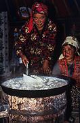 Kazakh woman heating curd<br /> Mongolia's largest ethnic minority<br /> near Tsengel Khairkhan Mountain<br /> Western Mongolia